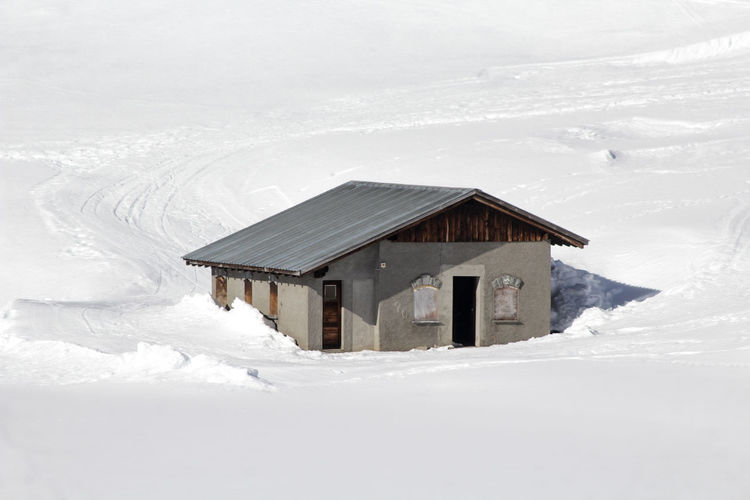 House on snow covered field against buildings