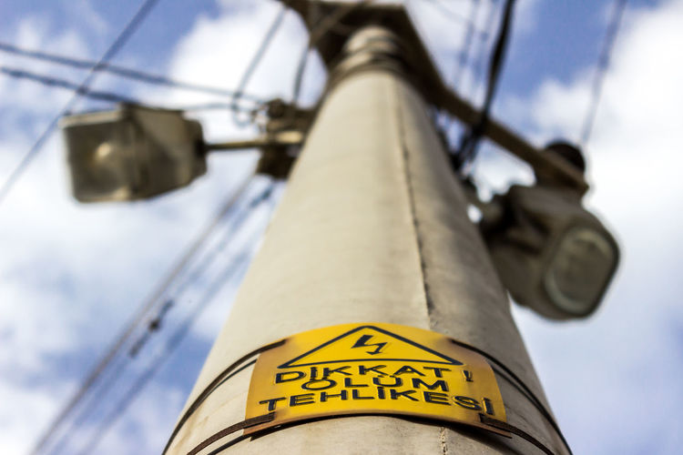 Low Angle View Of High Voltage Sign On Power Line