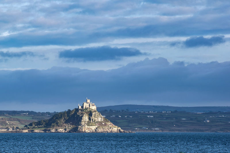 St Michael's Mount - Mount's Bay, Cornwall. A lovely walk over along the causeway when it's low tide. And enjoy a boat back when tide is in. A castle and church surrounded in beautiful gardens. Mounts Bay History In Cornwall EyeEm Best Shots EyeEmBestPics St Michael's Mount Looking From Penzance Mountain Place Of Worship History Sky Architecture Building Exterior Built Structure Shore Castle Calm Fort Idyllic Tranquility Waterfront Horizon Over Water