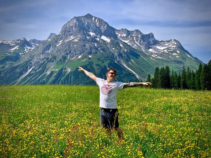 Smiling man standing on flowing land with arms raised against rocky mountain