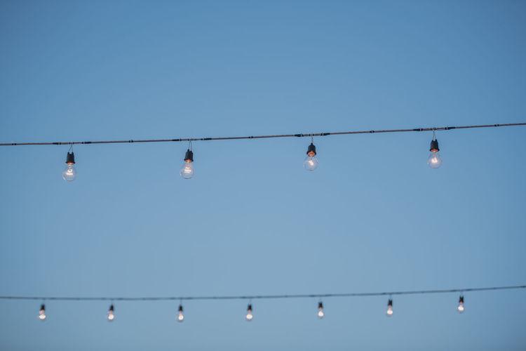 Low Angle View Of Illuminated Light Bulbs Hanging Against Clear Sky