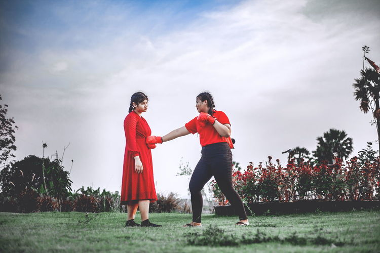 Beautiful two chubby teens exercise with muay thai or thai boxing in red clothes against covid 19