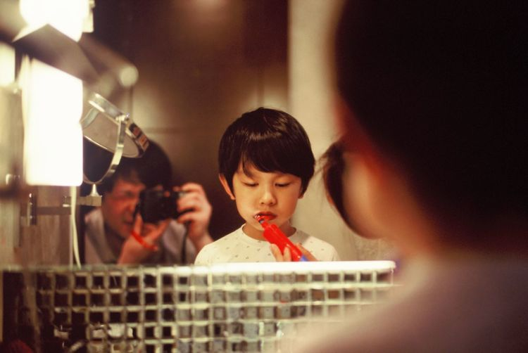 Father photographing while son brushing teeth in bathroom