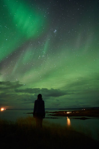 Rear view of man on lake against sky at night