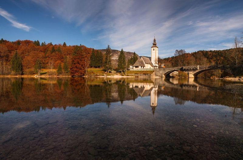 Church Of St John By Lake Bohinj Against Sky During Autumn