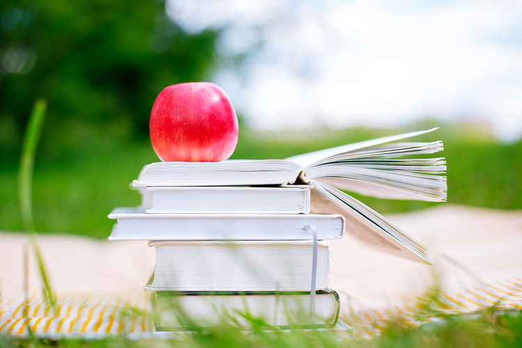 Close-up of apple on stacked books