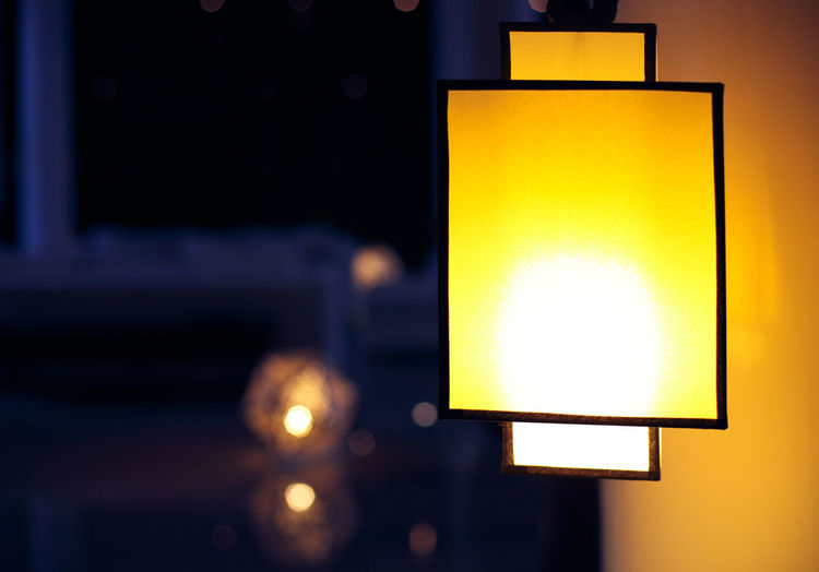 Close-up of illuminated light bulb at home