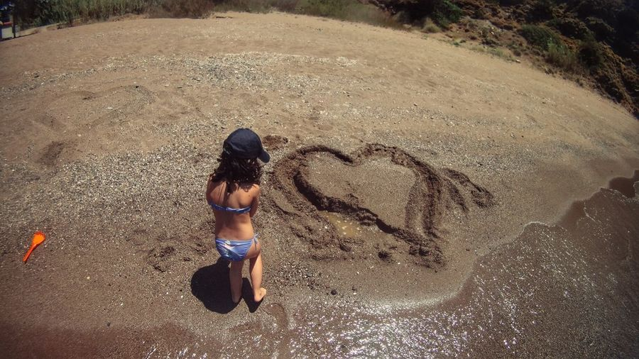 Rear View Of Girl Standing By Heart Shape On Sand At Beach