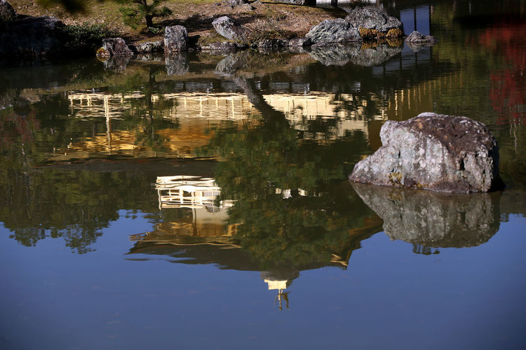 Reflection of rocks on lake against buildings