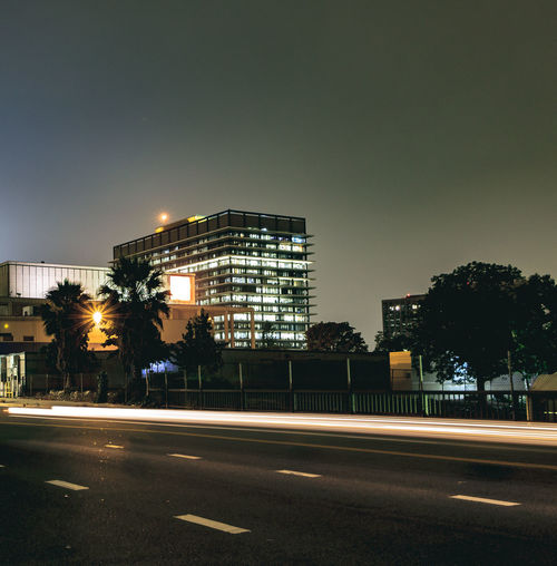 Light Trail in front of Building on Road Architecture Building Exterior Built Structure City City Street Cityscape Illuminated Motion Night No People Outdoors Road Sky Street Transportation Tree Urban Road Adapted To The City