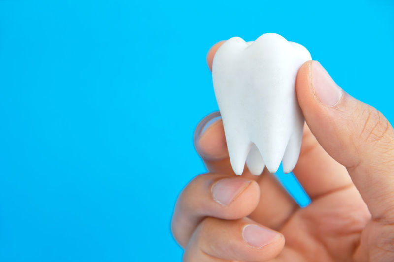 Cropped hand holding dentures against blue background