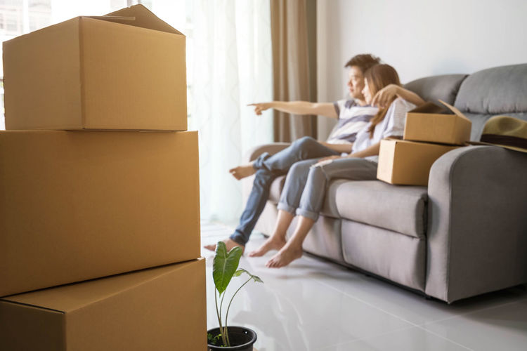 Young happy couple moving in new home, sitting and relaxing on safa with cardboard boxes Couple Unpacking Apartment Box Box - Container Cardboard Cardboard Box Casual Clothing Decoration Domestic Life Domestic Room Furniture Home Interior Home Ownership Indoors  Lifestyles Living Room Moving House Packing Real People Sitting Sofa Young Adult