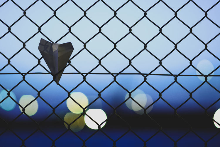 Paper airplane on chainlink fence against sky