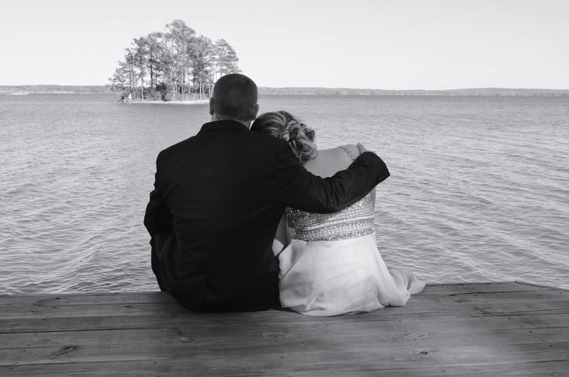 Rear view of wedding couple relaxing on jetty against lake