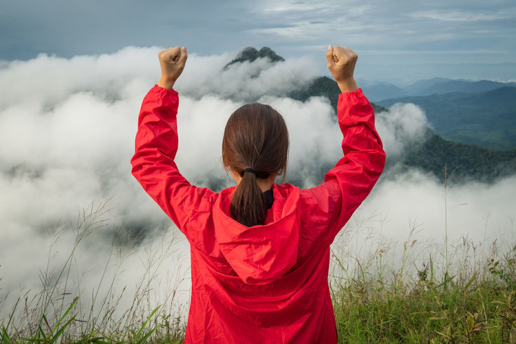 Rear view portrait of young woman standing outdoors with open arms on mountain peak Aerial Portrait Outdoors Freedom Limb Hairstyle Plant Scenics - Nature Real People Day Leisure Activity Sky Red Water Waist Up Beauty In Nature Standing Adult Nature Women Arms Raised Rear View Cloud - Sky Human Arm One Person International Women's Day 2019