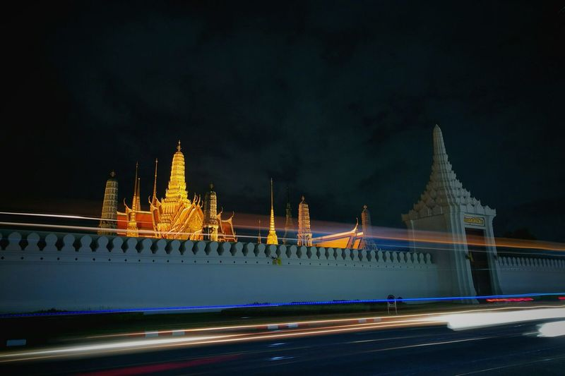 Light trails over street by wat phra kaeo against sky at night