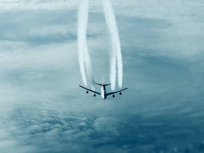 Low angle view of airplane in flight against sky