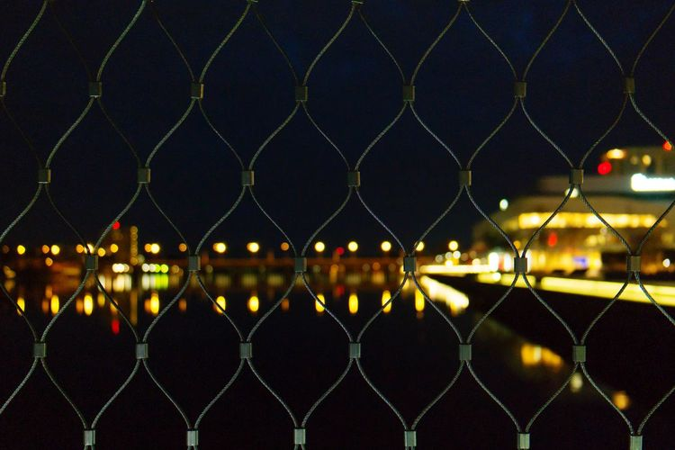 Close-up of chainlink fence against illuminated city at night
