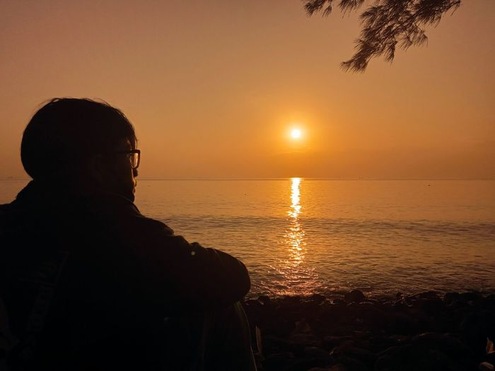 Silhouette man looking at sea against sky during sunset