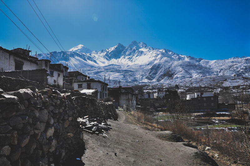 Snow Covered Buildings By Mountain Against Blue Sky