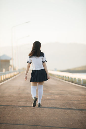 Rear view of woman wearing uniform while walking on road against sky