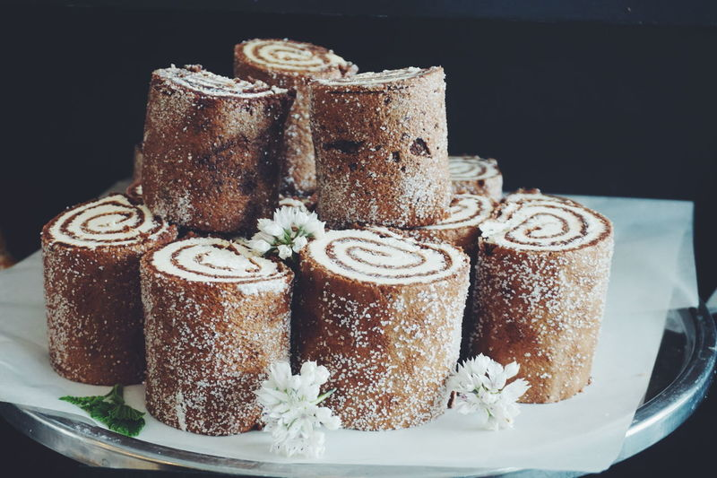 Swiss rolls decorated with flowers in plate against black background
