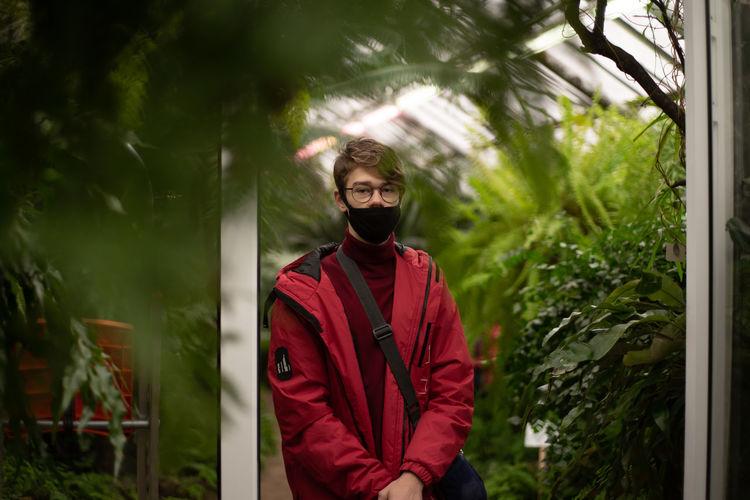 Portrait of teenage boy wearing mask standing against plants