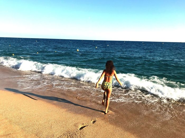 Sea Horizon Over Water Beach Water Sand One Person Clear Sky Scenics Rear View Beauty In Nature Nature Full Length Real People Tranquil Scene Wave Day Sunlight Vacations Outdoors Leisure Activity