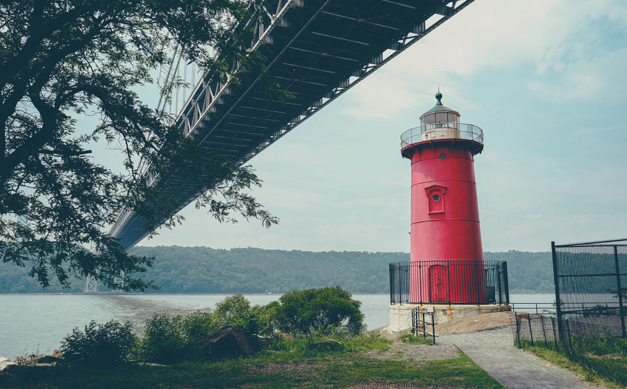 the lighthouse. Architecture Building Exterior Built Structure Calm Direction Footpath Green Color Guidance Lake Lighthouse Nature No People Outdoors Protection Red Safety Scenics Shore Sky Tall - High Tower Tranquil Scene Tranquility Tree Water