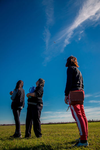 Looking to the sky Young Women Friendship Full Length Togetherness Women Standing Men Blue Sky Grass Hands In Pockets Posing