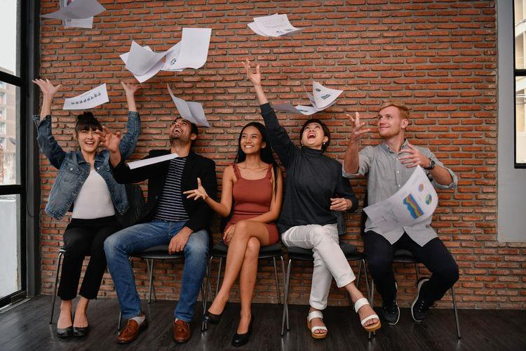 Cheerful coworkers throwing documents while sitting on chairs in office