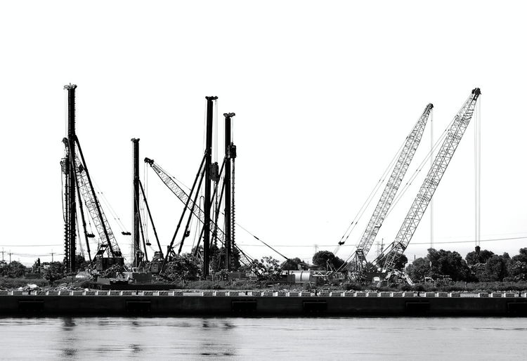 Drilling rigs and cranes seen in silhouette at a construction site Construction Site Silhouette Steel Cable Water Reflections Construction Equipment Crane - Construction Machinery Drilling Rig Industry Machinery Steel Structure  Water