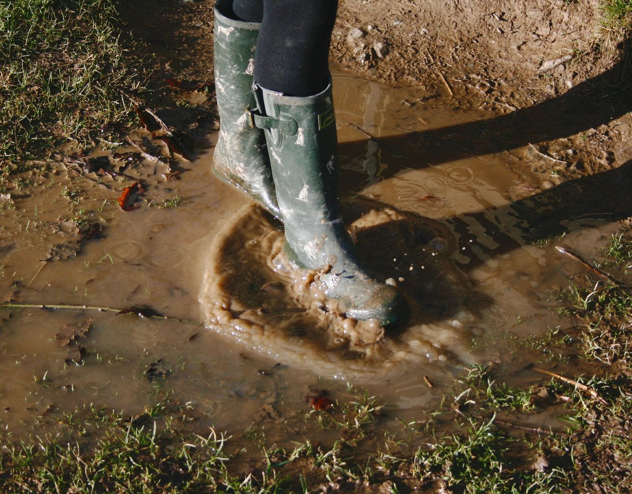 low section, real people, human leg, day, mud, water, lifestyles, one person, outdoors, men, motion, nature, working, grass, people