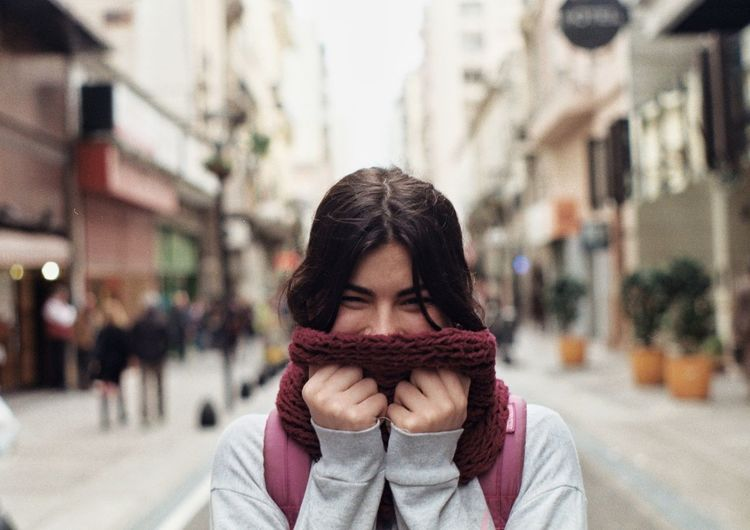 Portrait Of Young Woman Holding Scarf Against Face