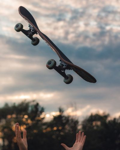 Close-up of hand catching skateboard against sky during sunset