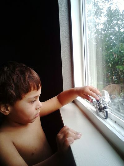 Shirtless Boy Playing With Toy Motorcycle On Window At Home