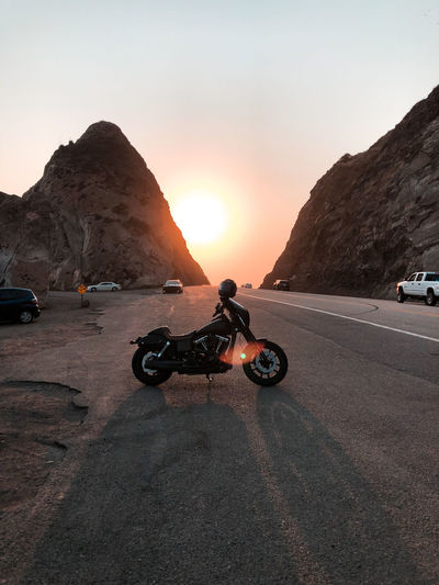 Motorcycle on road by rock formation against sky during sunset