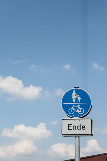 Low angle view of road sign against cloudy sky on sunny day