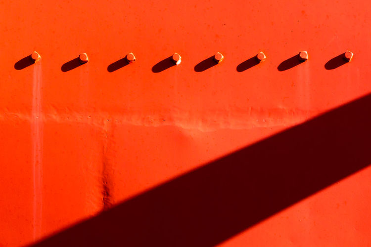 Full frame shot of red wall with shadow