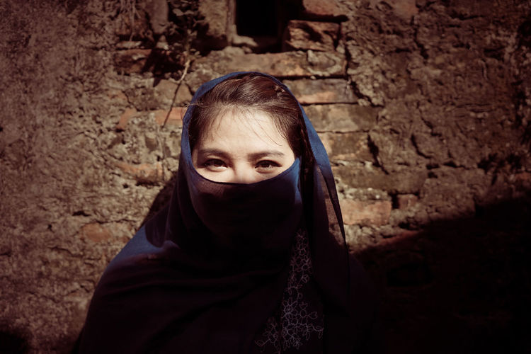 Portrait of young woman covering face