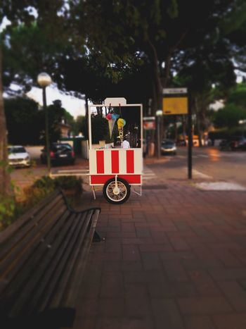 Bench City Life Ice On The Way Stripes Travel Wheel City Evening Ice Cream Ice Cream Truck Italy Milano Marittima No People Outdoors Portable Red White Selective Focus Shop Street Street Photography Transportation Travel Destinations Tree