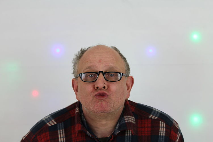 Portrait of mature man wearing eyeglasses while puckering against wall