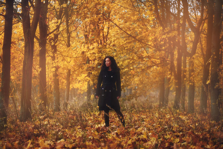 Full length of woman standing in autumn forest