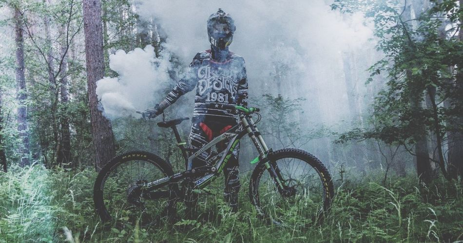 Man with mountain bike holding smoke bomb in forest