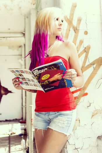 Young Woman With Dyed Hair Wearing Shorts Holding Magazine