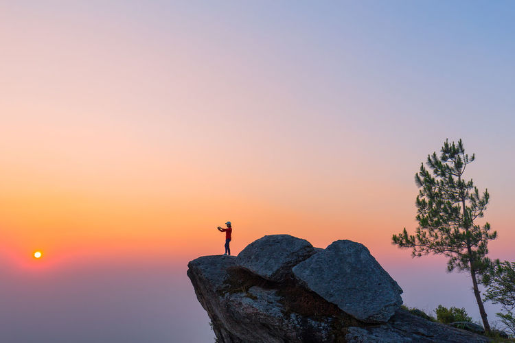 Person standing on rock against sky during sunset