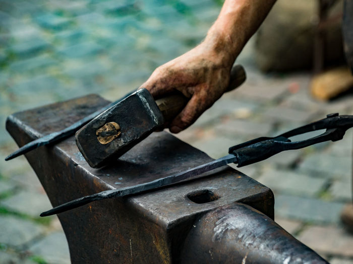 Close-up of man working on rusty metal