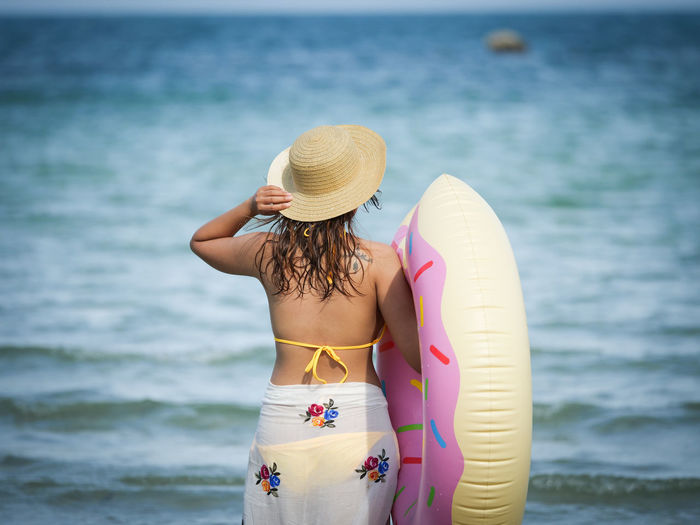 Rear view of woman wearing bikini carrying inflatable ring while standing at beach