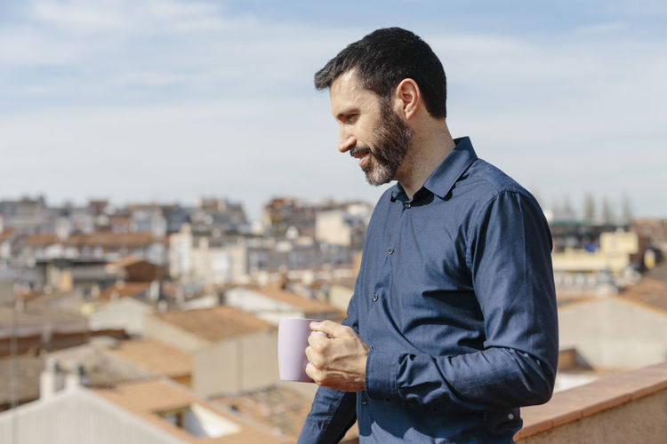 Young man drinking coffee with cityscape in background