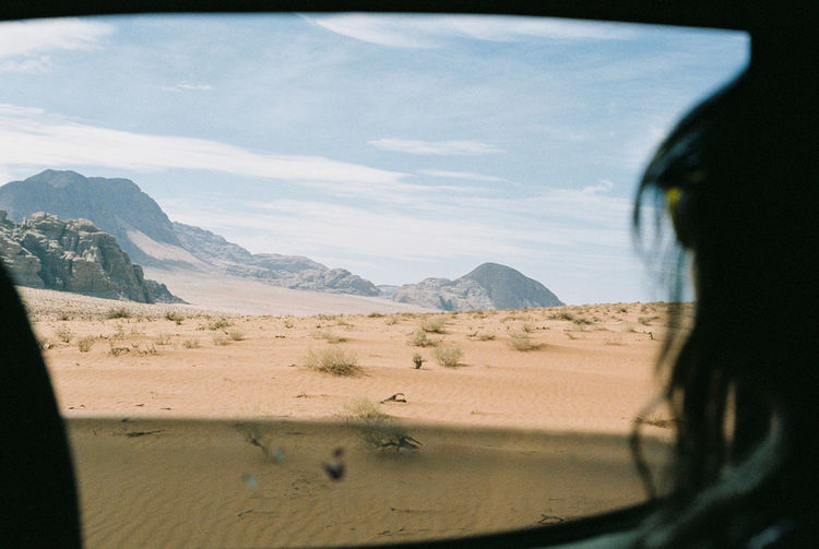 Close-Up Of Woman Looking At View Through Car Window In Desert